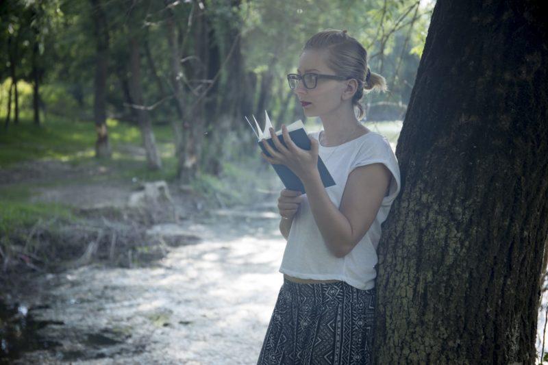 木に寄りかかって本を読んでいる外国人女性