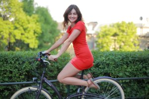 自転車にまたがっているワンピースの女性