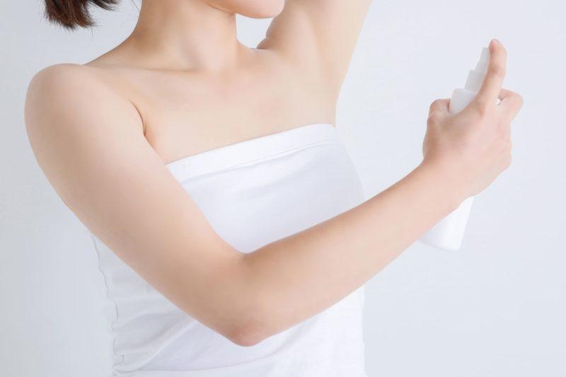脇に制汗剤をかけている女性