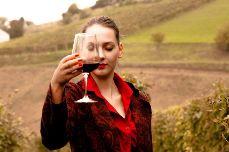 赤ワインを片手に飲んでいる赤い服の女性