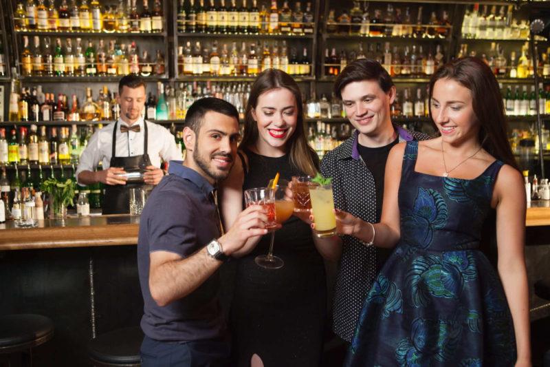 バーで乾杯している4人の若者
