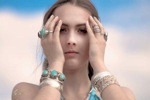 額に両手を当てているエメラルドグリーンの指輪をはめている外国人女性