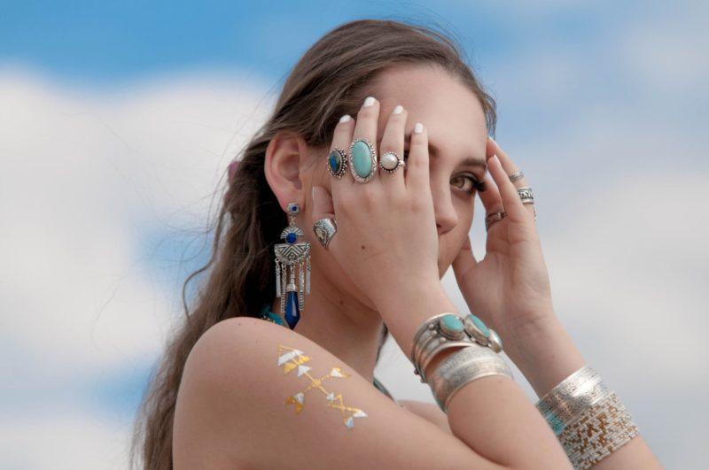 額に手を当てている様々なアクセサリーを身に着けている外国人女性