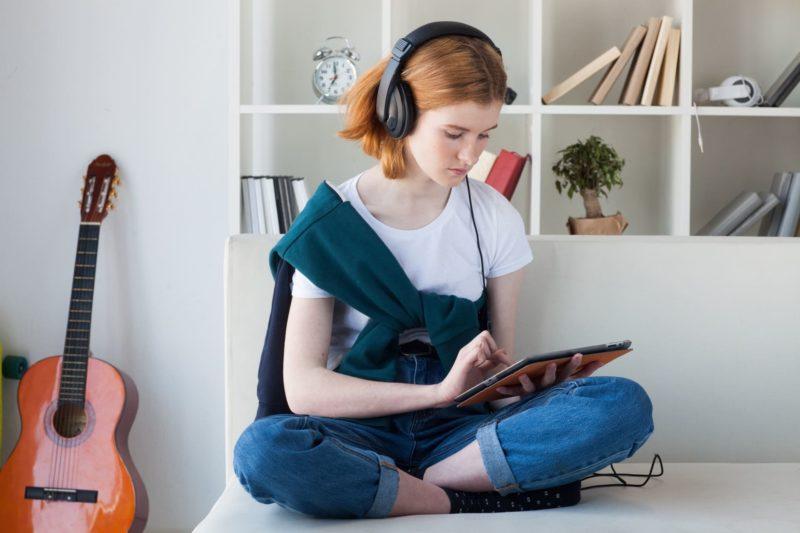 ベットの上でタブレットを操作している外国人女性