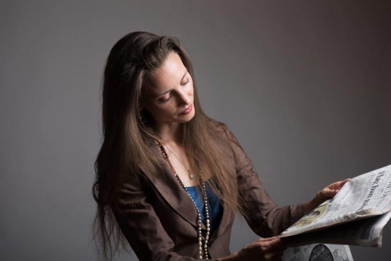 黒い背景の中新聞を読んでいる女性