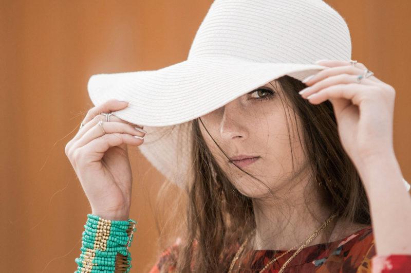 自分の顔を隠すように帽子をかぶっている女性