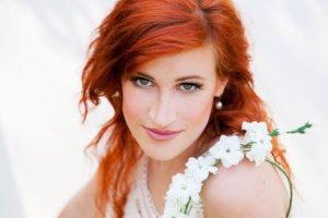 肩に白い花をかけたテラコッタ色の髪の女性