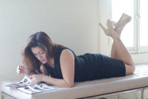 うつぶせで雑誌を読んでいる黒ワンピの女性