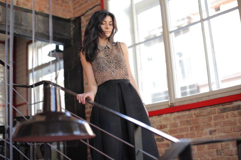 手すりにかを掛け、階段を降りようとしているヒョウ柄のノースリーブを着用した外国人女性
