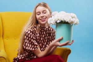 白い花を持ってうれしそうな女性