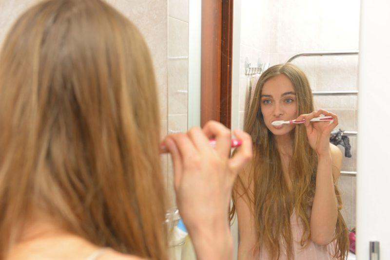 鏡に向かって歯磨きをする外国人女性
