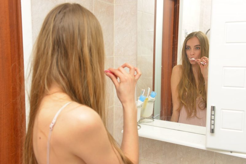 鏡に向かって歯磨きをしている茶髪で長髪の外国人女性