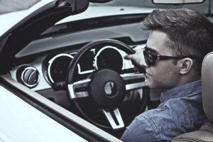 車の運転席に座ってステアリングを握っているサングラスを掛けた外国人男性