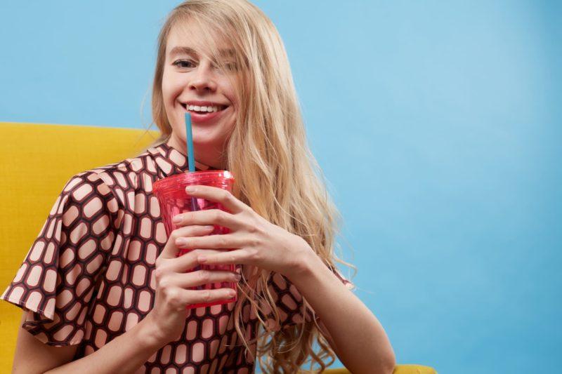 赤いプラスチックカップを持っている金髪で長髪の外国人女性