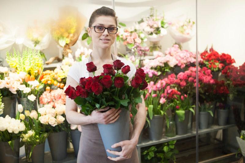 色とりどりの花屋でバラを売っている女性