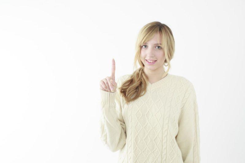 指を指している白いニットの女性