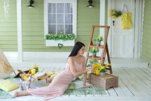 玄関先でお花を飾ってピクニックしている女性