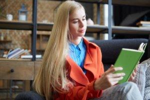 緑の表紙の本を読んでいる長髪の外国人女性