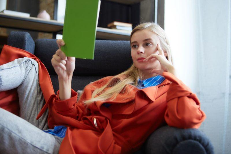 ソファでくつろぎながら緑の表紙の本を読んでいる外国人女性