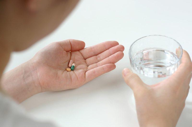 水が入ったコップとサプリメントを持ってサプリメントを飲もうとしている人