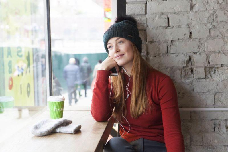カフェでくつろいでいる赤いニットの女性