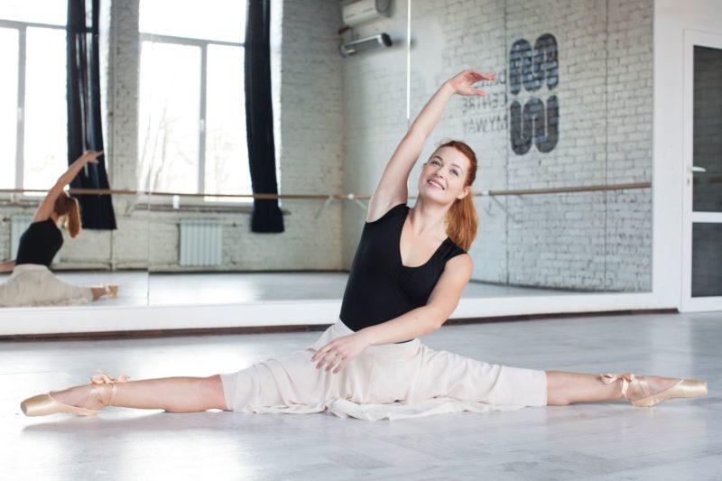 バレエで股割をしている外国人女性バレリーナ