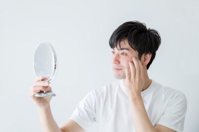 白地の背景で手鏡を使って顔の肌の様子を見る男性