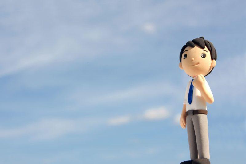 青空の下でガッツポーズをする男性ビジネスマンの人形