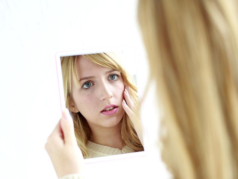 鏡をのぞいて悩む金髪の女性