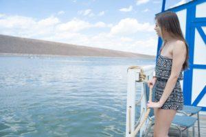 桟橋や船から海を眺めている女性