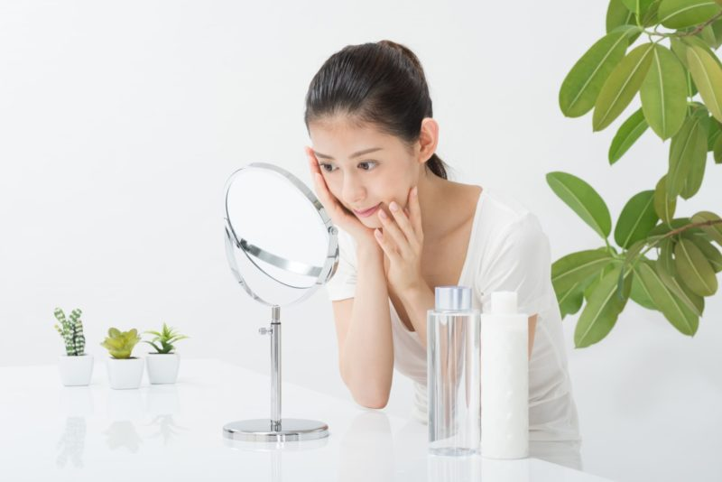 鏡を見ながらスキンケアを行っている女性