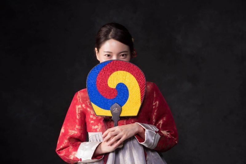 団扇で顔を隠している韓国人女性