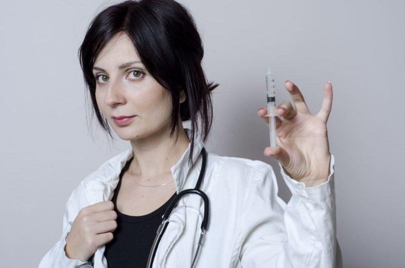 注射器を持っている外国人女性医師