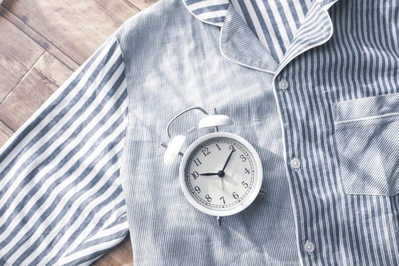 綿のパジャマと目覚まし時計