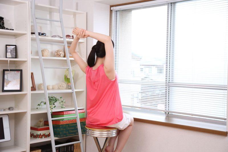 窓辺に座って伸びをしている女性