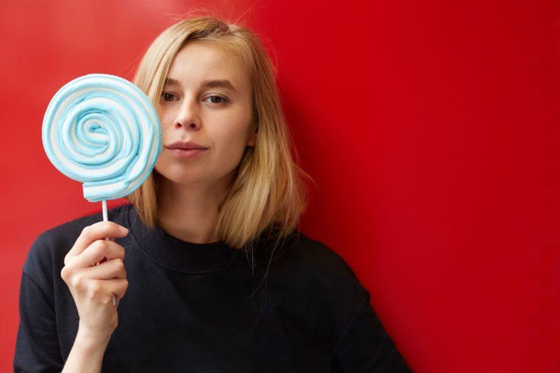青いキャンディーを舐めている女性