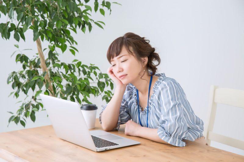 睡眠不足で仕事中に眠気が来ている女性