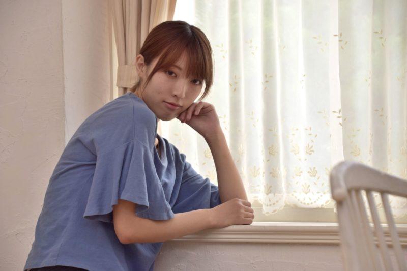 窓際に肘をついている女性