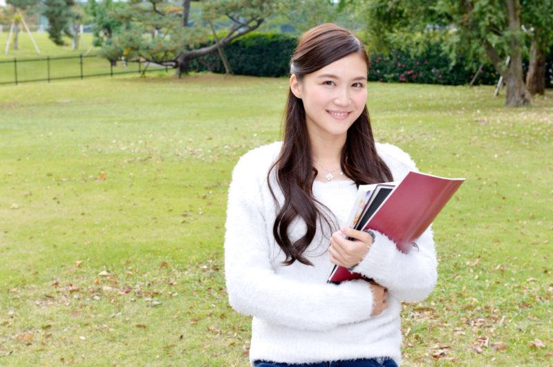 屋外でノートを持っている白い服を着用した女性