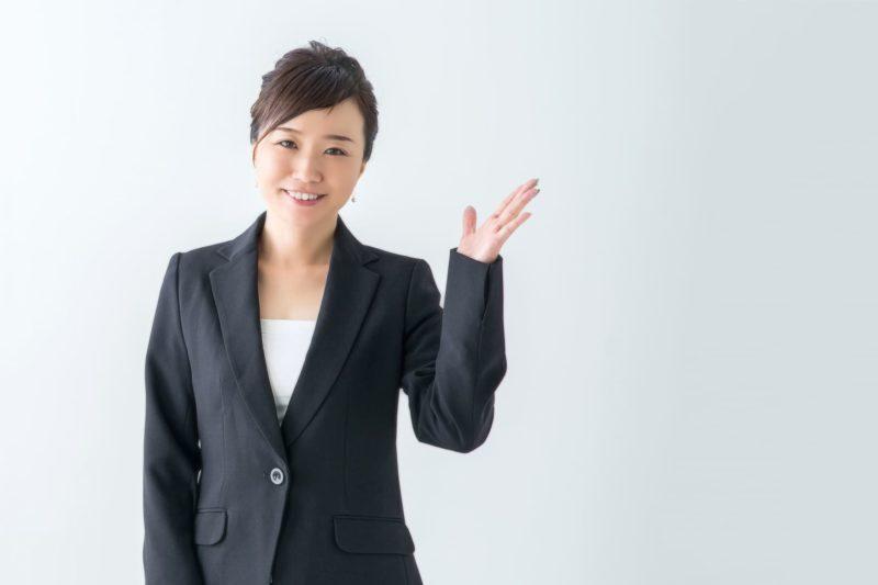 片手を上に挙げているスーツを着用した40代の女性