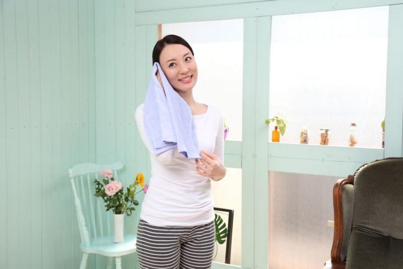 窓際で汗を拭いている白Tシャツの女性