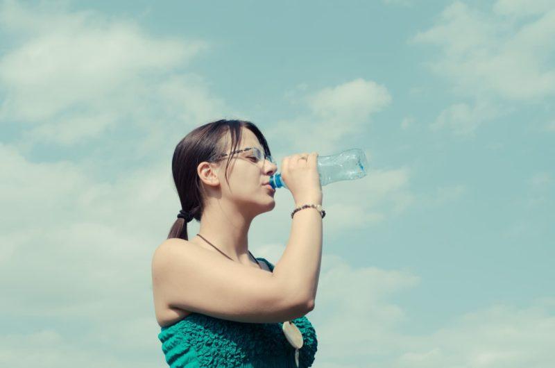 青空の下で女性が水を飲んでいる写真