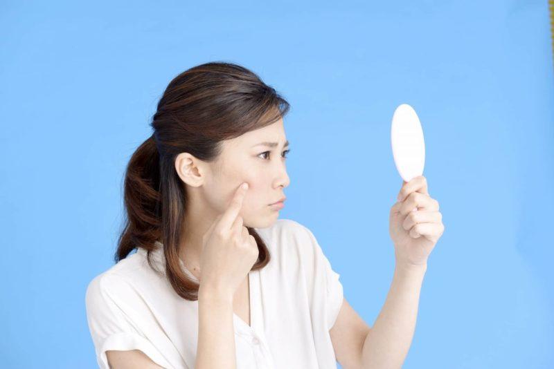 鏡を見て肌の状態を気にしている女性