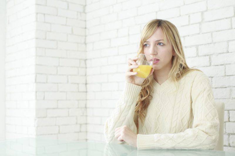 オレンジジュースを飲んでいる白ニットの女性