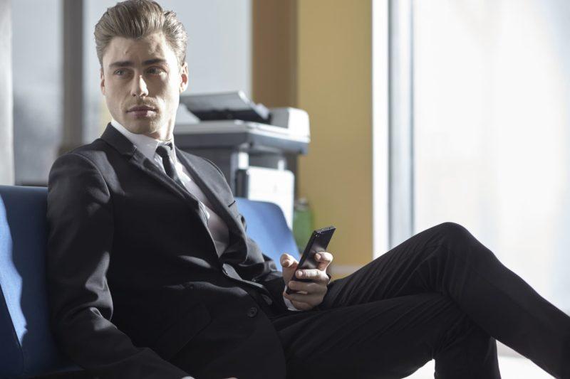 椅子に座ってスマートフォンを持っている外国人ビジネスマン