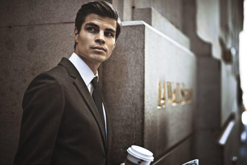 屋外でコーヒーが入ったカップを持っている外国人ビジネスマン