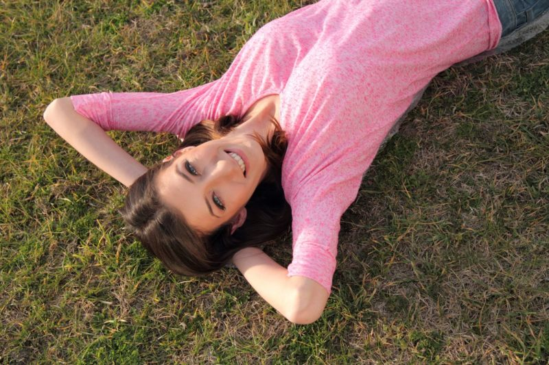 芝生で寝転がっているピンクのTシャツの女性