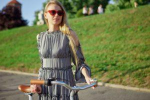 自転車を支えているサングラスをしたノースリーブのワンピースを着用した外国人女性
