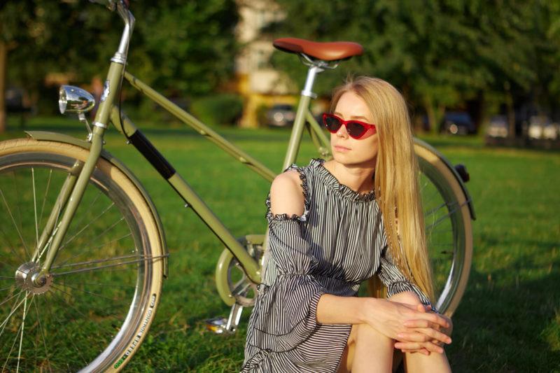 自転車を置いて座っているサングラスをしたノースリーブのワンピースを着用した外国人女性