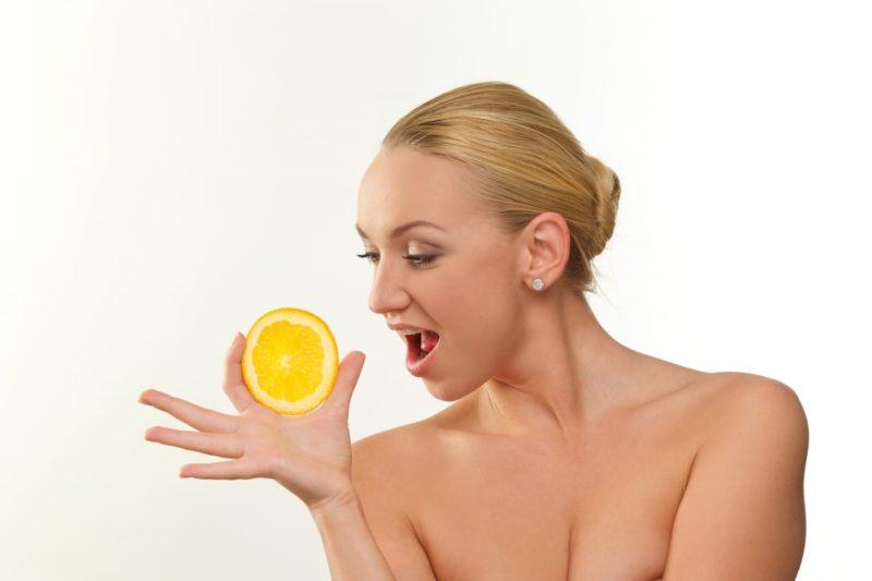 オレンジを持ちながら驚いている女性